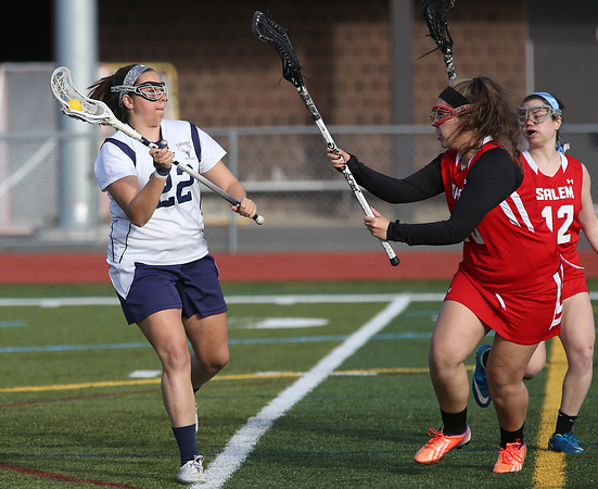 KEN YUSZKUS/Staff photo.   Peabody's Chole Gizzi, left, lets the ball fly at the Salem at Peabody girls lacrosse game.       04/29/16