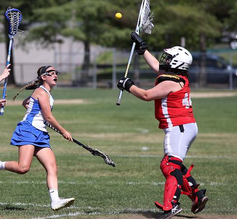 KEN YUSZKUS/Staff photo.          Danvers' Isabel McKenna shoots, but the Wakefield goalie Mikayla White blocks it during the Wakefield at Danvers girls lacrosse tournament game.            05/31/16