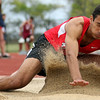 DAVID LE/Staff photo. Marblehead senior Michael Button sprays up sand as he lands in the pit during one of his long jumps in the final round. 5/21/16.