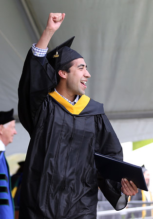 DAVID LE/Staff photo. Endicott College graduate Jorge Bernal Trejo pumps his fist in the air after receiving his diploma on Saturday morning. 5/21/16.