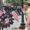 DAVID LE/Staff photo. Steve Godzik salutes a wreath he just placed down in Danvers Square on a rainy Memorial Day Monday. 5/30/16.