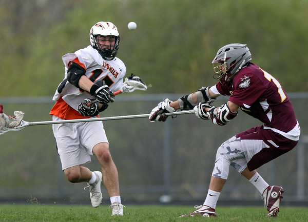 DAVID LE/Staff photo. Ipswich junior captain Charlie Gillis (17) fires a goal past the outstretched stick of Newburyport junior Rob Federico, right, on Friday afternoon. 5/13/16.