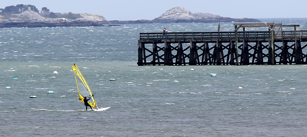 KEN YUSZKUS/Staff photo.   Taking advantage of the windy Monday, Dave Winslow windsurfs in Salem Harbor.     05/16/16