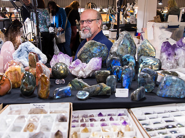PARKER FISH/ Photo. Warren Gonzales looks over his colorful collection of gems, and crystals during the Annual New England Gem and Mineral Show. 4/30/16