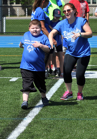 AMY SWEENEY/Staff photo.  Zachary McLaughlin, 8,  from Riverside Elementary School, plays kick ball with the help of aide Cate Yacubian during the Special Olympics Danvers Day Games on Friday, May 19, at Danvers High School J. Ellison Morse Athletic Complex at Dr. Deering Stadium. The games are being held for all special needs children in the Danvers Public Schools grades K-12 and surrounding local communities.