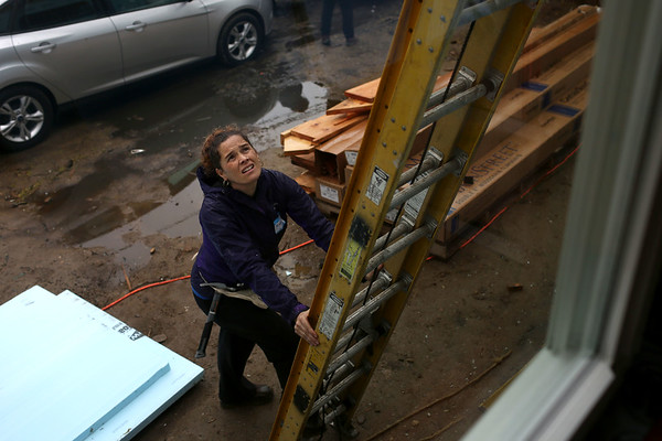 HADLEY GREEN/ Staff photo<br /> Maria Benson holds a ladder for her husband Paul. Maria and Paul will be living in this house constructed by Habitat for Humanity on Asbury street in South Hamilton. 5/6/17
