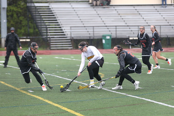 HADLEY GREEN/ Staff photo<br /> Bishop Fenwick's Cailyn Wesley (10) picks up the ball while Ipswich's Izzy Primack (16) and Kelsey Daily (2) guard her at the Bishop Fenwick v. Ipswich lacrosse game at Bishop Fenwick High. 5/5/17