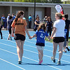 AMY SWEENEY/Staff photo. Erin Lally, left, a volunteer from Danvers High School, walks with Logan Meeny, 6, from Cove Elementary School in Beverly, and teacher Jessica Zigelbaum, as they walk to the starting line for a practice run. Danvers High School is hosting their Annual Special Olympics Danvers Day Games on Friday, May 19, at Danvers High School J. Ellison Morse Athletic Complex at Dr. Deering Stadium. The games are being held for all special needs children in the Danvers Public Schools grades K-12 and surrounding local communities.