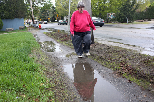 HADLEY GREEN/ Staff photo<br /> Nancy Verrocchi of Peabody walks on the sidewalk near the site of a water main break on Lowell Street in Peabody that erupted Monday afternoon.