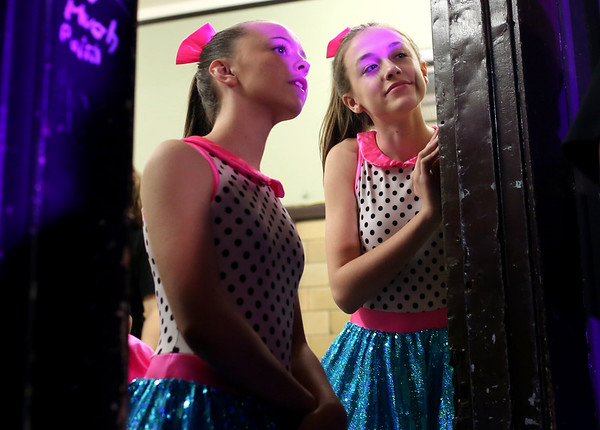 HADLEY GREEN/ Staff photo<br /> Ali Pheulpin and Emma Costain, who have been dancing at Mitchell's Dance Studio since they were little, peek at dancers onstage during the annual recital Saturday held at Briscoe Middle School in Beverly. 5/20/17