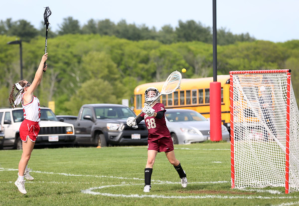 HADLEY GREEN/ Staff photo<br /> Newburyport goalie Molly Laliberty  (38) passes to teammates after making a save while Masconomet's Liv McCarthy (21) tries to block her at the Masconomet v. Newburyport girls varsity lacrosse game at Masconomet High School. 5/23/17