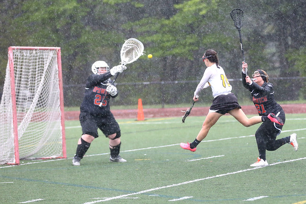 HADLEY GREEN/ Staff photo<br /> Bishop Fenwick's Ally Charette (16) shoots while Ipswich goalie Emily Martineau (25) prepares to make a save at the Bishop Fenwick v. Ipswich lacrosse game at Bishop Fenwick High. 5/5/17