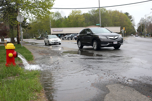 HADLEY GREEN/ Staff photo<br /> Cars drive by a fire hydrant that was spewing water after a water main break erupted on Lowell Street in Peabody on May 1st, 2017.