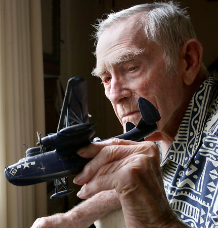 Hardy Prince holds a model of the plane he flew during World War II
