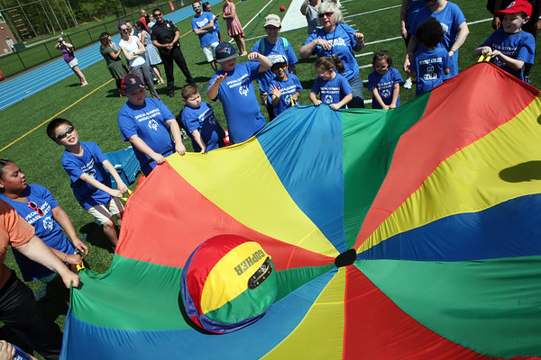 AMY SWEENEY/Staff photo. A group of students and teachers from Riverside Elementary School in Danvers toss a ball around the parachute during the Annual Special Olympics Danvers Day Games on Friday, May 19, at Danvers High School J. Ellison Morse Athletic Complex at Dr. Deering Stadium. The games are being held for all special needs children in the Danvers Public Schools grades K-12 and surrounding local communities.