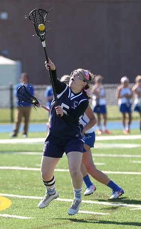 HADLEY GREEN/ Staff photo<br /> Peabody's Lauren Wolff (5) jumps for the ball at the Danvers v. Peabody girls varsity lacrosse game at Danvers High School. 5/10/17