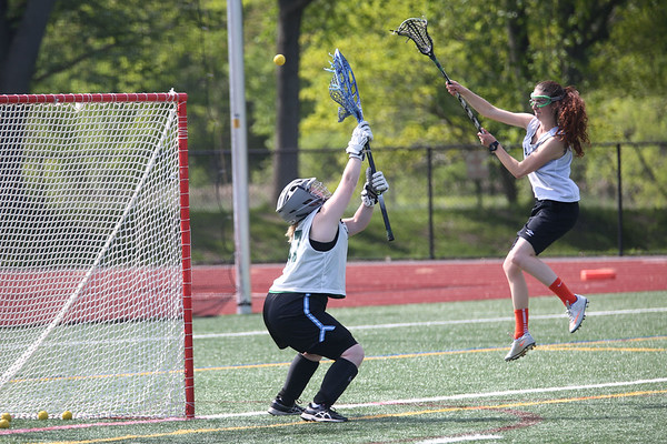 HADLEY GREEN/ Staff photo<br /> Ella Epiess shoots past goalie Cindy Bova during a drill at the Essex Tech girls lacrosse practice at Essex Technical High School in Danvers. 5/24/17