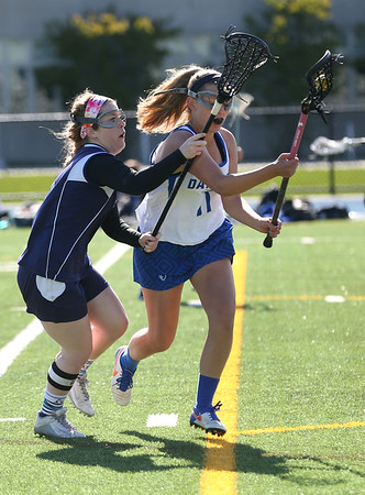 HADLEY GREEN/ Staff photo<br /> Peabody's Lauren Wolff (5) plays defense while Danvers' Shelby Johnson (11) runs with the ball at the Danvers v. Peabody girls varsity lacrosse game at Danvers High School. 5/10/17