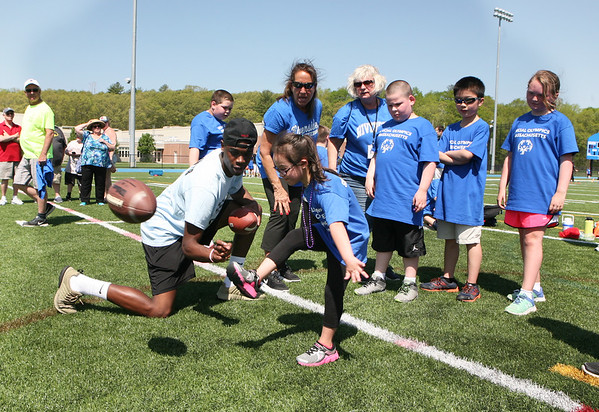 AMY SWEENEY/Staff photo. Lexi Millerick, 7, from Riverside Elementary School, gets ready to kick a football with the help of Tahg Coakley, a junior at Danvers High School. The high school hosted their Annual Special Olympics Danvers Day Games on Friday, May 19, at Danvers High School J. Ellison Morse Athletic Complex at Dr. Deering Stadium. The games are being held for all special needs children in the Danvers Public Schools grades K-12 and surrounding local communities.