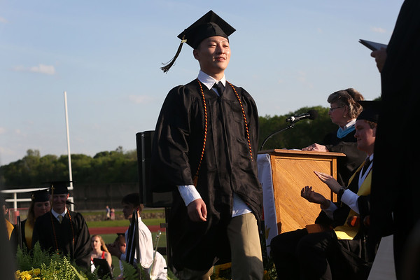 HADLEY GREEN/ Staff photo<br /> Graduating senior Qihang Tang walks across the stage to receive his diploma during the Bishop Fenwick High School graduation ceremony. 5/19/17