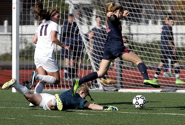 KEN YUSZKUS/Staff photo. Central's Elayna Grillakis jumps over the Lincoln-Sudbury goalie with her ball rolling toward a goal, but just misses because of the goalie's deflection during the Central Catholic High School vs Lincoln-Sudbury Regional High School girls soccer match at Manning Field in Lynn. 11/11/14