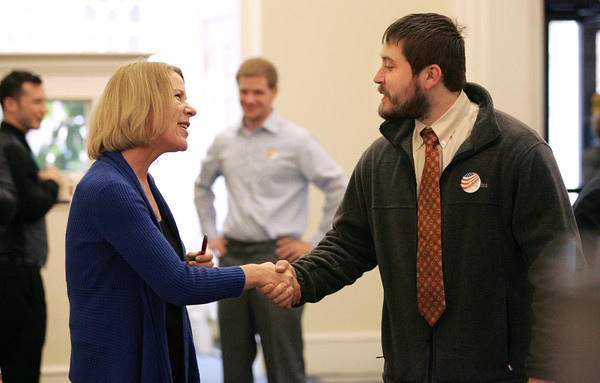 KEN YUSZKUS/Staff photo.  Marjorie Longo of BenePlan and North Shore Career Center and Jared Smith of Lynn say goodby after conversing at the HIRE-A-VET conference held at the Salem Five bank. It was a job fair for veterans.   11/10/15.