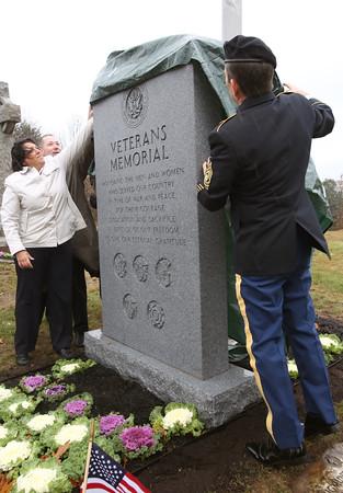 KEN YUSZKUS/Staff photo.  Salem Mayor Kim Driscoll, left, along with Salem Veterans Officer Kim Emerling unveil the new Salem Veterans memorial at St. Mary's Cemetery on Veterans Day.   11/11/15.
