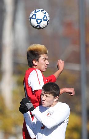DAVID LE/Staff photo. Masco senior Blaise Romanowski leaps over Oliver Ames senior Max Ahern to win a header. 11/21/15.