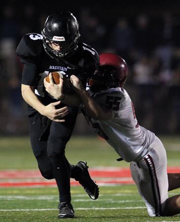 DAVID LE/Staff photo. Marblehead senior quarterback Garret Keough (13) powers through a tackle from Gloucester senior linebacker Thomas Donahue (55). 11/6/15.