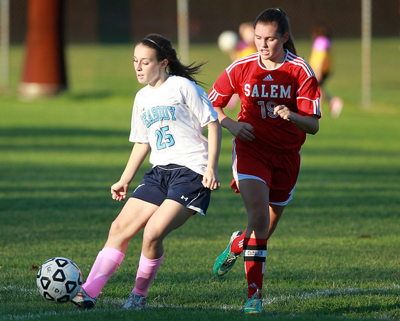 Peabody freshman Jillian Arigo (25) plays the ball upfield while being chased down by Salem senior captain Katherine Towey (19). DAVID LE/Staff photo. 10/17/14.