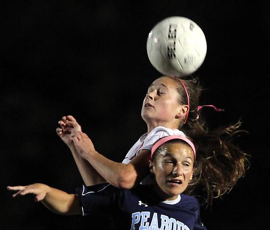 DAVID LE/Staff photo. Marblehead junior Olivia Eddy leaps over Peabody senior Katrina Silva to win a header. 10/14/15.