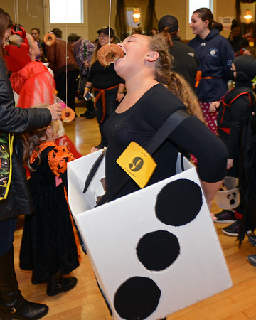 RYAN HUTTON/ Staff photo<br /> Mairead Walsh, 11, competes in the donut-on-a-string contest while dressed like a die at the Peabody Halloween celebration at the Knights of Columbus hall on Thursday.