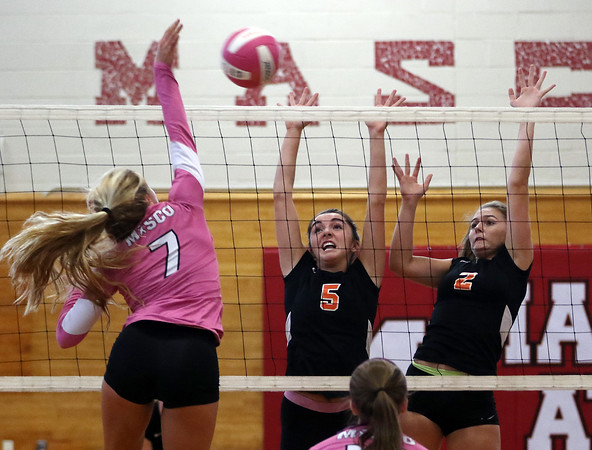 DAVID LE/Staff photo. Beverly senior Maeve Blake (5) and junior Katie Noonan (2) leap high in the air as they try and block a spike from Masco sophomore Ryder Burliss (7). 10/4/16.