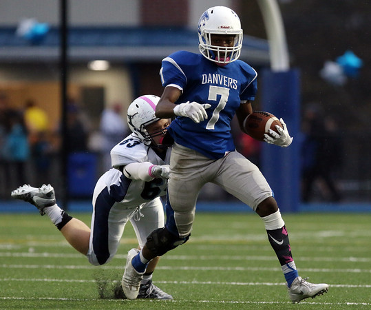 DAVID LE/Staff photo. Danvers senior Tahg Coakley (7) gets dragged down from behind by Peabody junior Cam Powers (63). 10/21/16