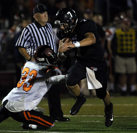 DAVID LE/Staff photo. Marblehead quarterback Drew Gally jukes his way past Beverly safety Kevin Flaherty (33) 10/7/16.