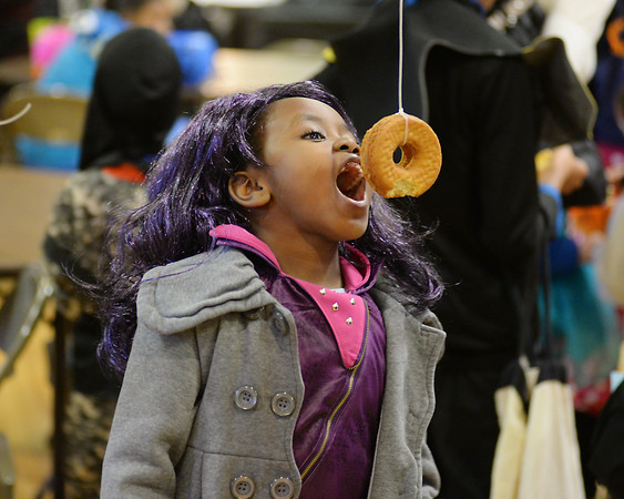 """RYAN HUTTON/ Staff photo<br /> Dressed as the character Mal from the Disney Channel show """"Descendants"""", Tiffany Nvuta, 7, competes in the donut-on-a-string eating contest at the Peabody Halloween celebration at the Knights of Columbus hall on Thursday."""