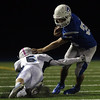 DAVID LE/Staff photo. Danvers senior captain Quin Holland (33) sidesteps a tackle from Peabody junior Nolan Murphy (5). 10/21/16