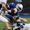DAVID LE/Staff photo. Danvers senior Tahg Coakley gets dragged down by Peabody junior Cam Powers (63). 10/21/16