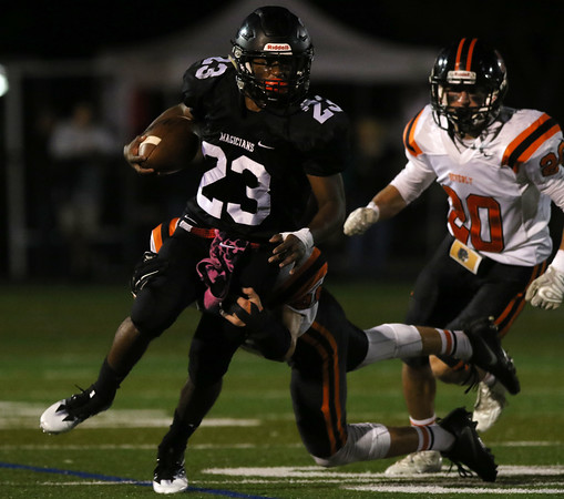 DAVID LE/Staff photo. Marblehead senior running back Jaason Lopez tries to power his way through a diving Beverly defender during the first half of play. 10/7/16.