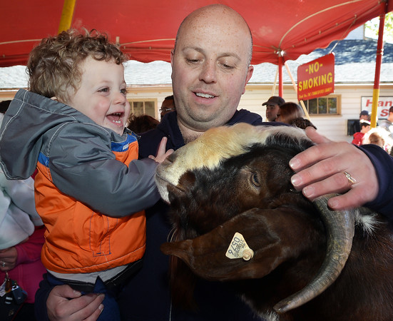 CARL RUSSO/Staff photo. After a rainy Sunday, thousands of people came out to enjoyed themselves on the last day of the 198th. Topsfield Fair. America's oldest fair. Chris Sawyer of Danvers and his son Vince, 2 pet the goat in the petting zoo. 10/10/2016