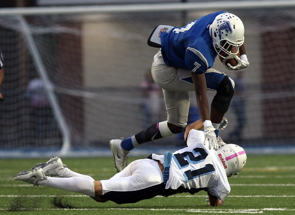 DAVID LE/Staff photo. Danvers senior Tahg Coakley leaps over Peabody senior Cedric Gutierrez (21) while throwing a stiff arm during the first half of play. 10/21/16