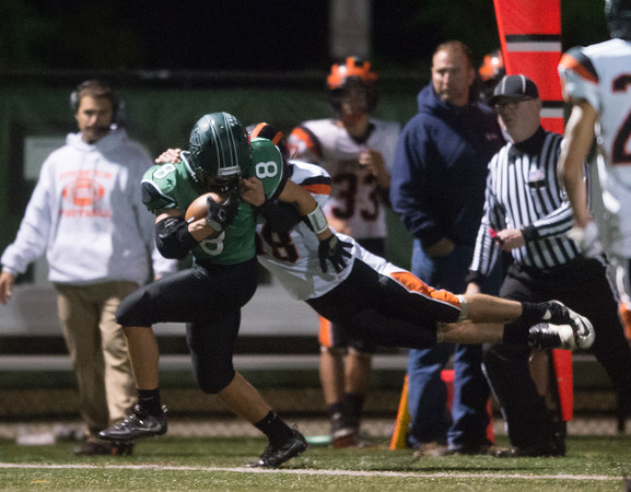 Desi Smith Photo.   Ipswich's Jack Sotiropoulos (18) makes a flying tackle along the sidelines on Manchester's RB Robbie Samanian (8) Friday night at Hyland Field in Manchester. October 14, 2016.