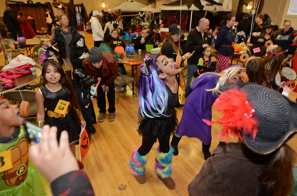 RYAN HUTTON/ Staff photo<br /> Jaylene Ortiz, 12, competes in the donut-on-a-string eating contest at the Peabody Halloween celebration at the Knights of Columbus hall on Thursday.
