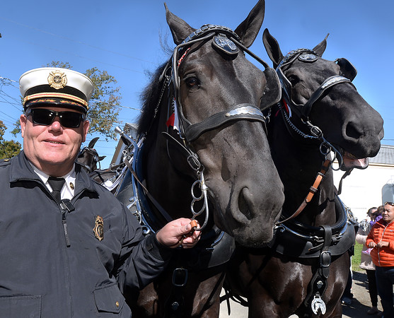 CARL RUSSO/Staff photo. After a rainy Sunday, thousands of people came out to enjoyed themselves on the last day of the 198th. Topsfield Fair. America's oldest fair. Topsfield Fire Chief, Ron Giovannacci got a special retirement gift from the fair; a ride in the wagon pulled by the Percheron Draft Horses around the fair grounds. A firefighter for 37 years, 18 years as chief, Giovannacci poses with two of the six draft horses before their show.  10/10/2016