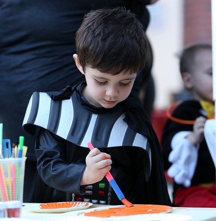 DAVID LE/Staff photo. Four-year-old Logan Bates, of Sale, paints a wooden mask orange at a craft table during Mayor's Night Out in Salem on Friday afternoon. 10/7/16.
