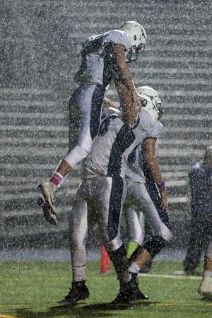 DAVID LE/Staff photo. Peabody junior Randdye Ramos, right, lifts up senior quarterback Matt D'Amato after his QB keeper touchdown run. 10/21/16