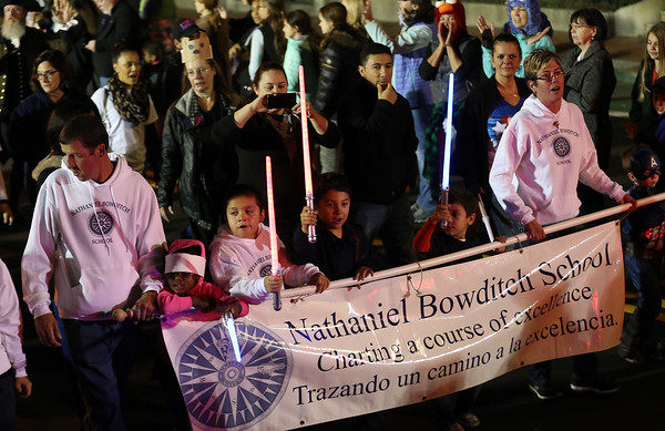 DAVID LE/Staff photo. Students and supporters of the Nathaniel Bowditch School carried a banner and light sabers towards the end of the Haunted Happenings Parade. 10/6/16.