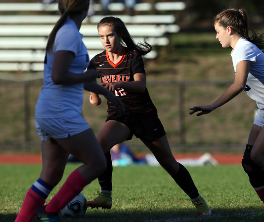 DAVID LE/Staff photo. Beverly freshman Klaudia Rushi (12) moves through a patch of sunlight while controlling the ball against Swampscott. 10/6/16.