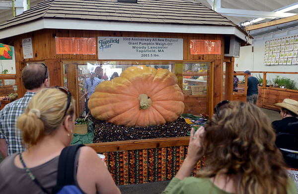 RYAN HUTTON/ Staff photo<br /> Visitors to the Topsfield Fair's vegetable barn on Monday check out this year's award winning 2,003.5 pound pumpkin, grown by Topsfield's own Woody Lancaster.