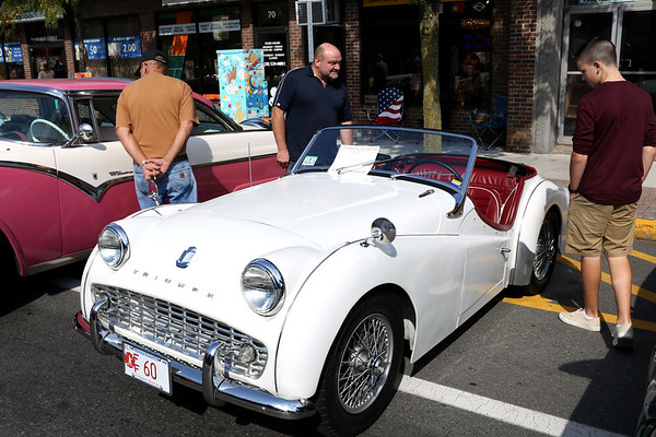 HADLEY GREEN/Staff photo<br /> People admire a 1960 Triumph Tr3a at the annual classic car show and craft fair along Main Street in Peabody. 10/07/17